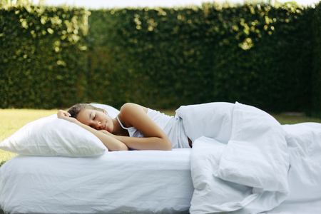 Tienermeisje slapen op zachte matras en kussen op gras buiten. Gezond ontspannen op een gezellig bed op frisse lucht in de tuin.