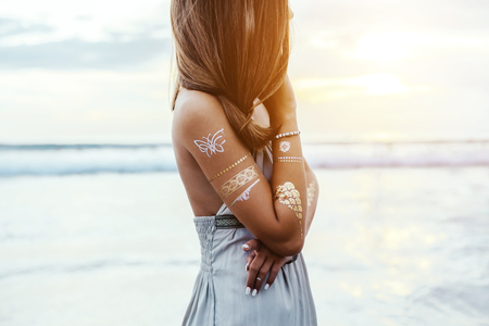 Young teenage girl with silver tattoo and boho jewelry over shore on sunset