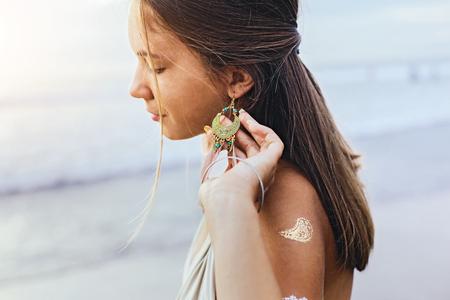 Jeune adolescente avec tatouage en argent et boucles d'oreilles boho au-dessus du rivage au coucher du soleil Banque d'images