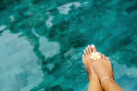 Woman relaxing in swimming pool in Bali luxury resort. Foot spa and pedicure lifestyle photo, topv view.