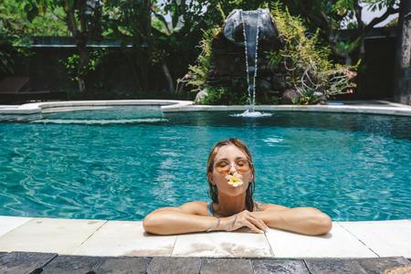 Womanrelaxing in outdoor swimming pool in Bali luxury resort 写真素材