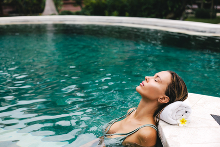 Woman relaxing in outdoor swimming pool in Bali luxury resort Stok Fotoğraf