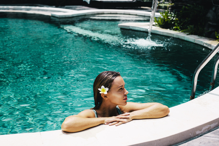 Woman with flower in her hair relaxing in outdoor swimming pool in Bali luxury resort