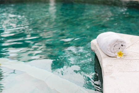 Towel and flower in luxury spa jacuzzi pool. Luxury tropical resort and wellness center.