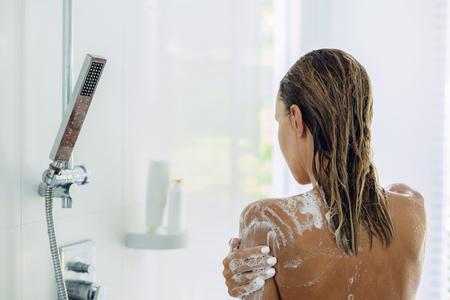 Rückansicht einer Frau, die morgens im modernen weißen Badezimmer duscht. Alltagslebensstilfoto.