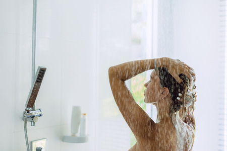 Back view of woman taking shower in modern white bathroom in the morning. Daily routine lifestyle photo. Imagens - 118570115