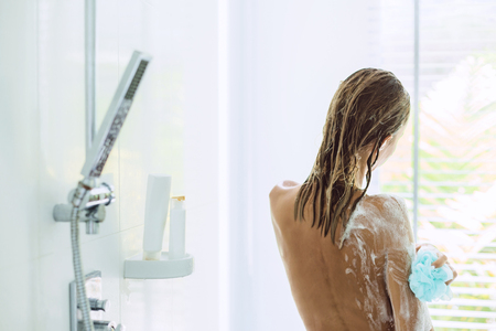 Back view of woman taking shower in modern white bathroom in the morning. Daily routine lifestyle photo.