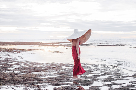 Beautiful elegant young lady in bohemian straw hat and red maxi dress walking on beach in sunlight Standard-Bild - 118570131