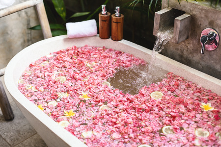 Bath tub with flower petals filling with water. Organic spa relaxation in luxury Bali outdoor bathroom. Фото со стока