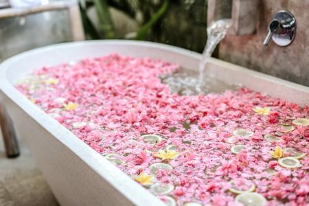 Badewannenfüllung mit Wasser mit Blumen und Zitronenscheiben. Organische Spa-Entspannung im luxuriösen Bali-Außenbad. Standard-Bild