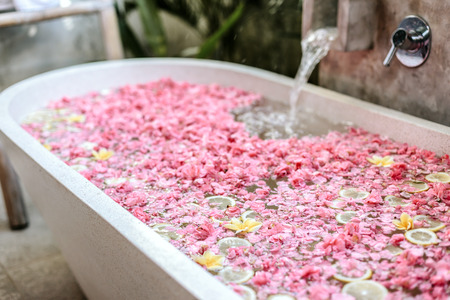 Bath tub filling with water with flowers and lemon slices. Organic spa relaxation in luxury Bali outdoor bathroom.