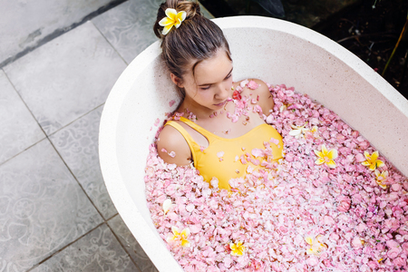 Young teenage girl relaxing in organic bath tube with tropical flowers in luxury Bali spa resort