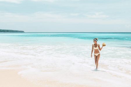 Woman in yellow bikini and sunglasses drinking fresh coconut juice while relaxing on sandy tropical beach. Healthy summer vegan diet concept. Stok Fotoğraf