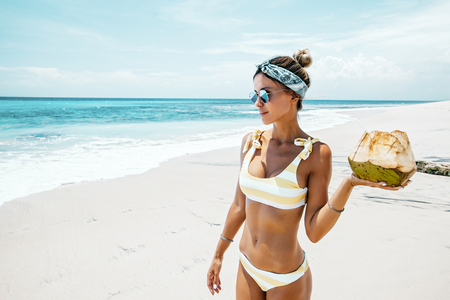 Woman in yellow bikini and sunglasses drinking fresh coconut juice while relaxing on sandy tropical beach. Healthy summer vegan diet concept. Stock Photo