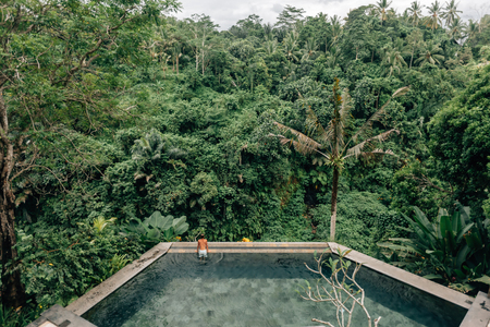 Human swimming in Bali infinity pool with jungle view in Ubud luxury resort Imagens