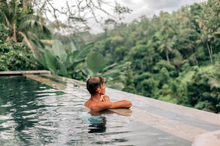 Human swimming in Bali infinity pool with jungle view in Ubud luxury resort Stok Fotoğraf