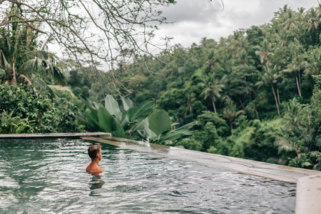 Human relaxing in Bali infinity pool with jungle view in Ubud luxury resort