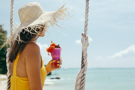 Teenage girl drinking fruit cocktail while hanging on swings with a sea view in beach cafe. Summer vacation on paradise island.