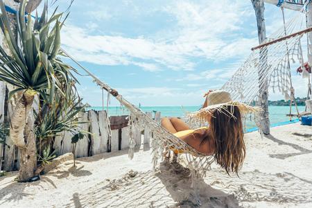 Dziewczyna relaksuje się w hamaku w kawiarni na tropikalnej plaży, gorący słoneczny dzień na rajskiej wyspie Zdjęcie Seryjne