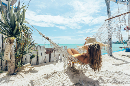 Girl relaxing in hammock in tropical beach cafe, hot sunny day at paradise island