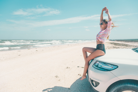 Girl feeling wind and freedom while relaxing at the beach. Car trip to summer holiday idyllic. Stock Photo - 120968616