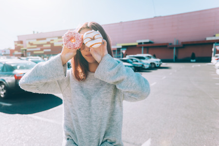 Teenage girl eating donut outside. Teenager with trendy street food near shopping mall. Фото со стока
