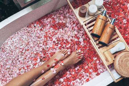 Female legs in bathtub with flower petals and beauty products on wooden tray. Organic spa relaxation in luxury Bali outdoor bath.