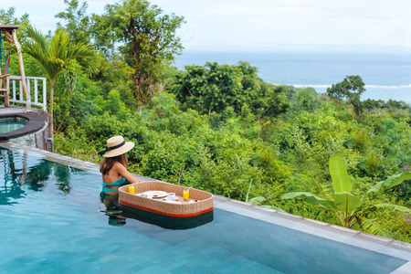 Girl relaxing and eating in luxury infinity pool with a view. Served floating breakfast in tropical Bali resort. Banco de Imagens