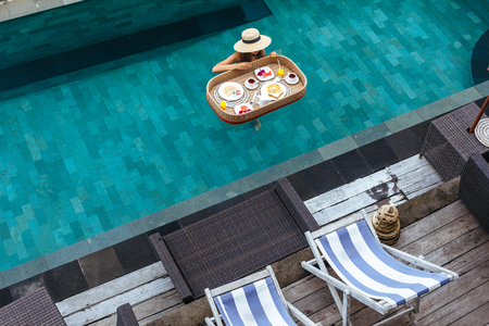 Girl relaxing and eating in luxury hotel pool. Served floating breakfast in tropical Bali resort. Archivio Fotografico