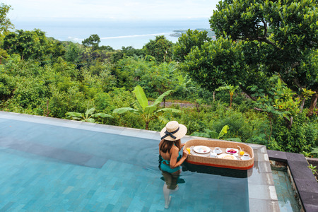 Girl relaxing and eating in luxury infinity pool with a view. Served floating breakfast in tropical Bali resort.