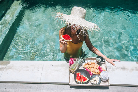 Girl relaxing and eating fruits in the pool on luxury villa in Bali. Exotic summer diet. Tropical beach lifestyle. Stok Fotoğraf