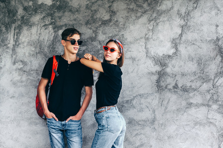 Hipster teen girl and boy wearing blank black t-shirt, jeans, headband and glasses posing against gray street wall. Same clothes look for teenage friends.