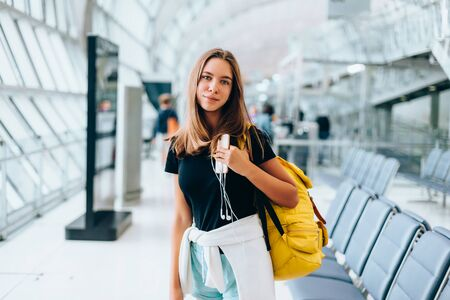 Teen girl waiting for international flight in airport departure terminal. Young passenger with backpack travelling on airplane. Teenager tourizm abroad alone concept. Фото со стока - 131557990