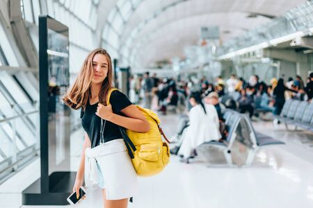 Teen girl waiting for international flight in airport departure terminal. Young passenger with backpack travelling on airplane. Teenager tourizm abroad alone concept. Фото со стока - 131557196