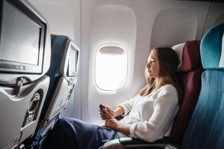 Teenager-Mädchen mit Medien an Bord während des Fluges. Junge Passagiere, die zum ersten Mal mit dem Flugzeug reisen.