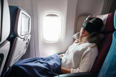 Adolescente durmiendo en boad durante el vuelo. Pasajero joven que viaja solo en avión.