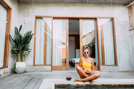 Girl relaxing and eating watermelon in the pool on luxury villa in Bali. Exotic summer diet. Tropical beach lifestyle. 版權商用圖片
