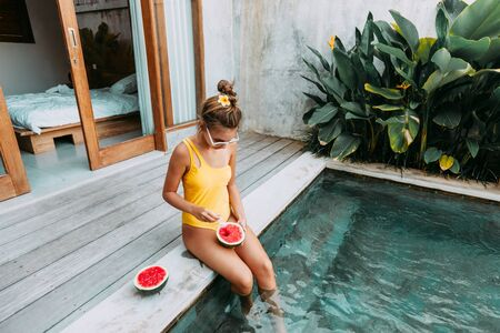 Girl relaxing and eating watermelon in the pool on luxury villa in Bali. Exotic summer diet. Tropical beach lifestyle. Archivio Fotografico
