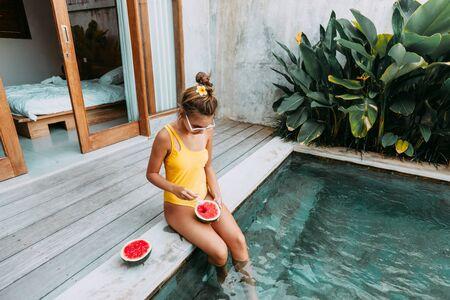 Ragazza che si rilassa e mangia anguria in piscina in una villa di lusso a Bali. Dieta estiva esotica. Stile di vita da spiaggia tropicale.