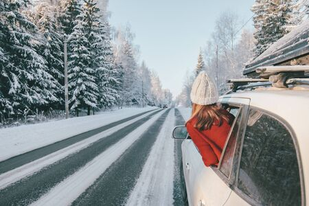 Rear view of teen girl in car over snowy forest on winter roadtrip to the nordic way Stockfoto