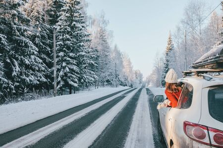 Rear view of teen girl in car over snowy forest on winter roadtrip to the nordic way Stock Photo