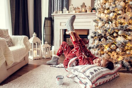 10 years old preteen girl in pajama and Santa hat laying on carpet with holiday bedding by Christmas tree and fireplace and drinking milk in morning at home