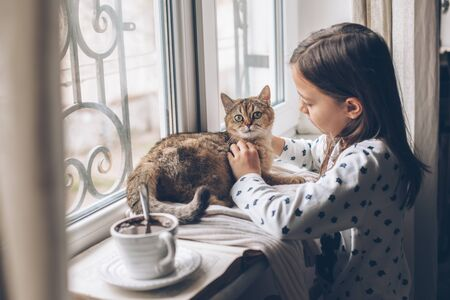 Child in pajamas relaxing on a window sill with pet. Lazy weekend with cat at home. Cozy scene, hygge concept. Imagens