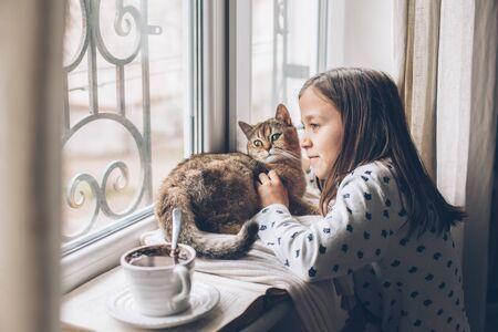 Kind in den Pyjamas, die auf einem Fensterbrett mit Haustier sich entspannen. Faules Wochenende mit Katze zu Hause. Gemütliche Szene, Hygge-Konzept.