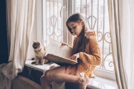 Child in warm woolen sweater seating on window sill and reading a book. Winter weekend with cat at home. Cozy scene, hygge concept. Zdjęcie Seryjne