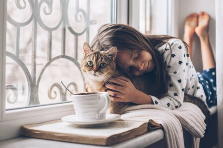 Child in pajamas relaxing on a window sill with pet. Lazy weekend with cat at home. Cozy scene, hygge concept. Foto de archivo
