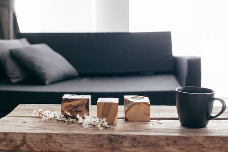 Spring home decor on rustic coffee table over black sofa with cushions. Grey vases and spring flowers on wooden bench in small dark room interior. Scandinavian home style. Zdjęcie Seryjne