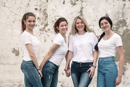 Group of four young diverse girls wearing blank white tshirt and jeans posing against rough street wall, fashion urban clothing style, mockup for t-shirt print store Imagens