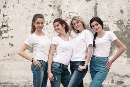 Group of four young diverse girls wearing blank white tshirt and jeans posing against rough street wall, fashion urban clothing style, mockup for t-shirt print store