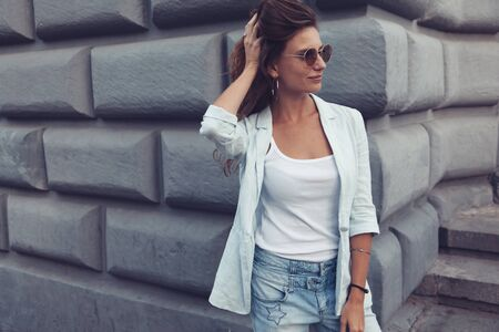 Fashion model wearing blue jacket and sunglasses posing in the city street. Fashion urban outfit. Casual everyday clothing style.